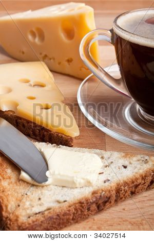 breakfast with coffee, cheese and butter on toasts