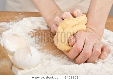 hands kneading dough on wooden table