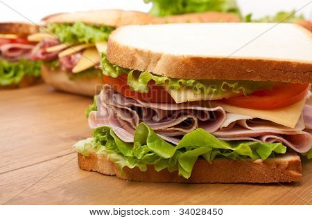 group of tasty sandwiches on a wooden table
