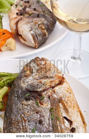 two servings of sea bream fish with vegetables on white plates