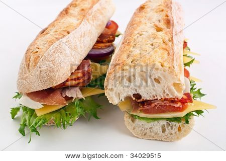 two halves of long white wheat baguette sandwich