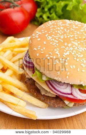 big tasty cheeseburger with french fries and ingredients on a wooden table