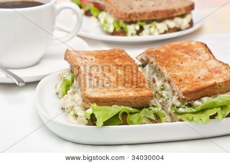 egg salad sandwiches on toasted bread and a cup of coffee