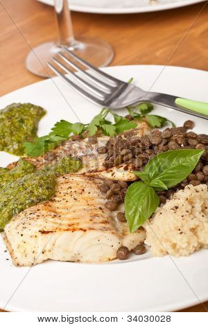 healthy baked tilapia fish garnished with lentil, couscous and pesto sauce