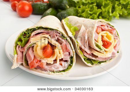 sanduíche de tortilla envolvido rolos corte ao meio e ingredientes
