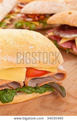 group of ciabatta bread sandwiches stuffed with meat, cheese and vegetables on a wooden table