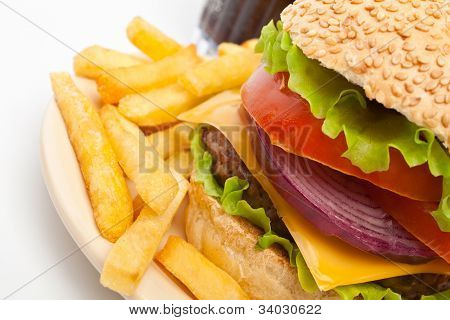 big cheeseburger garnished with french fries on a  plate and a glass of cola on white background