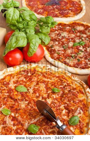 three different pizzas with basil, tomatoes and cheese on a wooden table