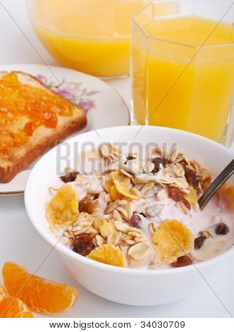 healthy breakfast meal - bowl of muesli with yoghurt ,  toast with jam and a glass of orange juice