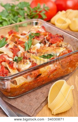 stuffed shell pasta with tomato sauce and cheese baked in a casserole dish and ingredients