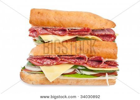 two halves of long baguette sandwich with lettuce, vegetables, salami and cheese on white background