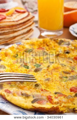 omelet  with ham, bacon and vegetables close up