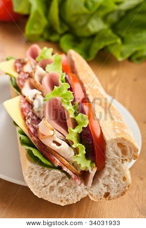 half of long tasty subway baguette sandwich with lettuce, tomatoes, ham, turkey breast, salami and cheese on cutting board with ingredients