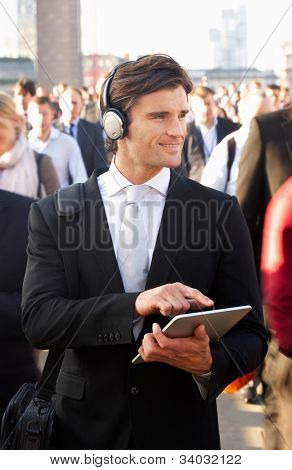 Male commuter in crowd with tablet and headphones
