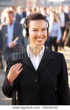 Female commuter in crowd wearing headphones