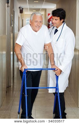 Happy senior man being helped by a male doctor to walk the Zimmer frame