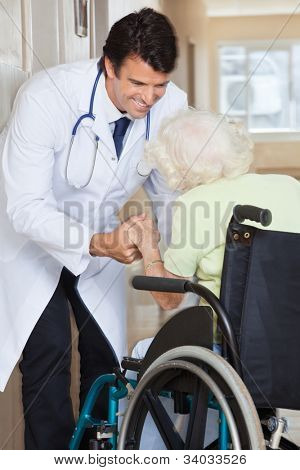 Happy young doctor assisting senior woman sitting in wheelchair at hospital