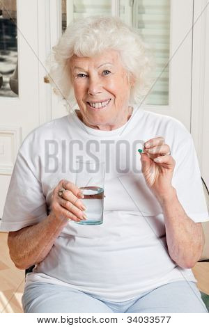Portrait of a senior woman taking a pill with a glass of water