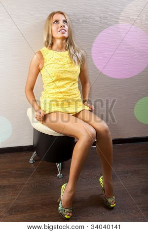 beautiful sexy woman in yellow dress sits near wall