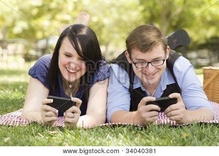 Attraktives junges Paar auf der Park-SMS auf ihre Smartphones zusammen.
