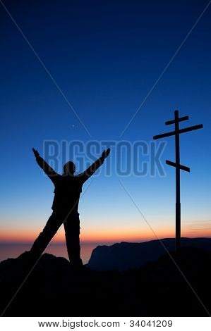 Man Near The Cross Against The Sky At Sunset