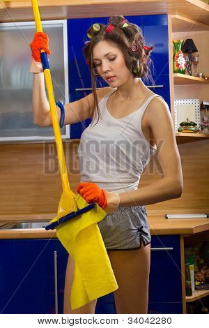 Smiling young woman change floor cloth and cleaning the floor at home