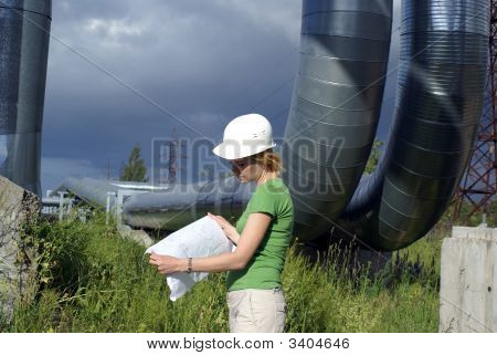 Woman Engineer Or Architect With White Safety Hat, Drawings And Industrial Pipelines On Background