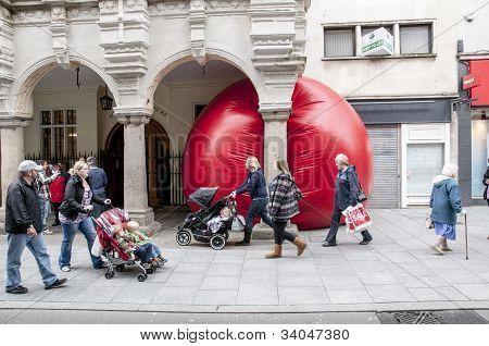 Transeúntes miran la bola gigante rojo de Kurt Perschke que se exprimió a la entrada de la Guildhal