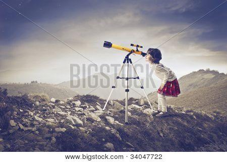 Niña mirando un telescopio en las montañas