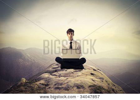 Jovem empresário sentado sobre uma colina e usando um laptop