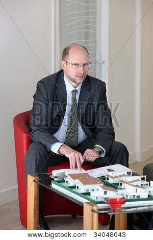 Architect sat with model housing