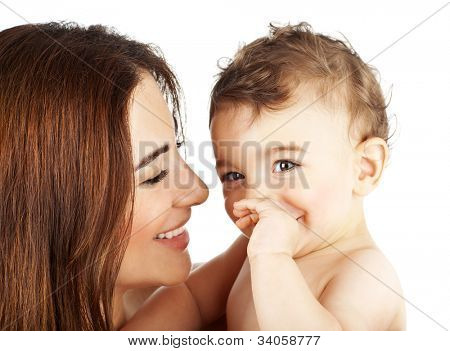 Adorable baby boy smiling with mother, closeup on happy family faces, mom and kid having fun indoor, parent holds little child in hands, healthy toddler and mommy portrait isolated on white background