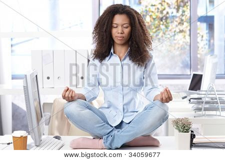 Casual ethnic office worker sitting on top of desk, relaxing eyes closed.