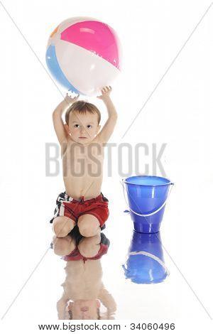 """Um preschooler adorável brincando com um balde de areia e bola de praia colorida pela """"beira da água,"""" sagacidade"""
