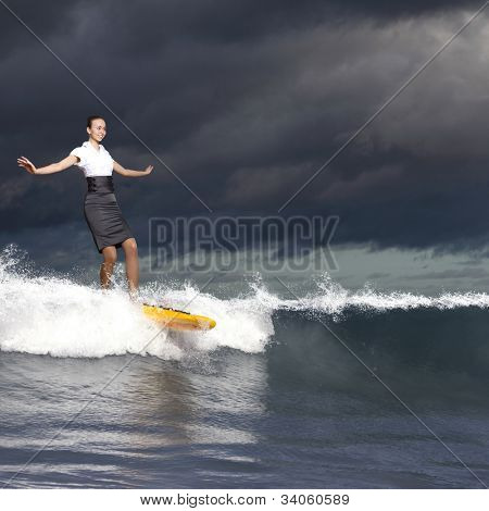 Image of young business person surfing on the waves of the ocean