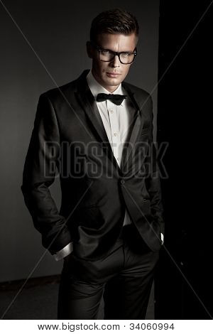 Elegant man posing on dark background