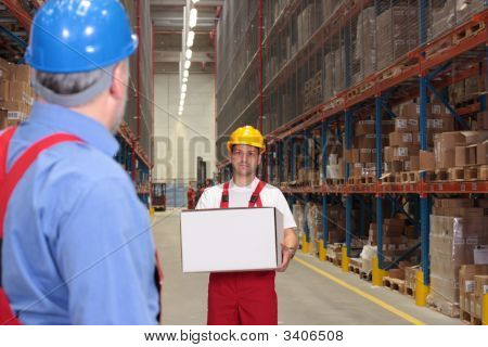 Worker Bringining Box In Warehouse
