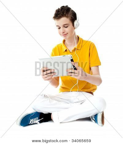 Seated Boy Watching Video On Tablet