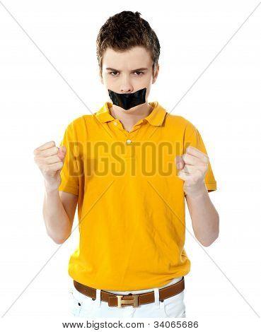 Niño enojado con cinta adhesiva en la boca.