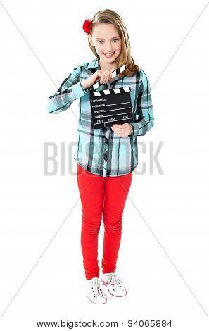 Sonriente chica sosteniendo la claqueta
