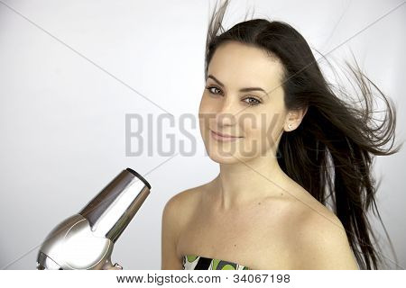 Young Female Model Blow Drying Her Long Silky Hair
