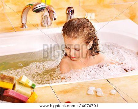 Little girl bathing in bubble bath .