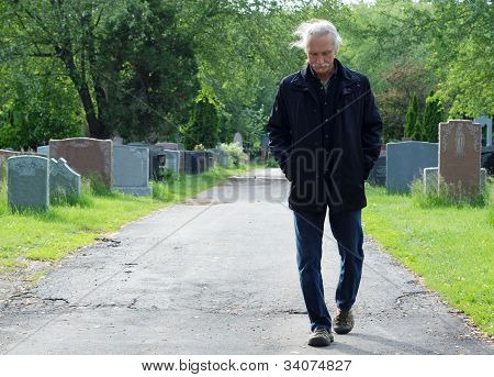 Man Walking In Cemetery