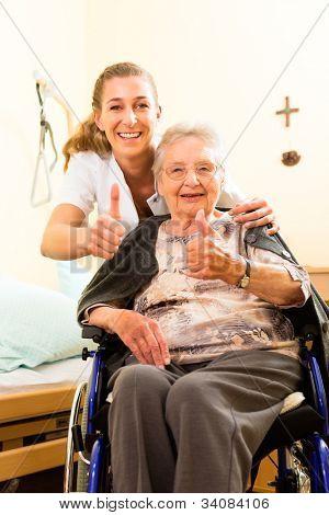 Junge Krankenschwester und weibliche Senioren im Pflegeheim, die alte Dame in einem Rollstuhl sitzen