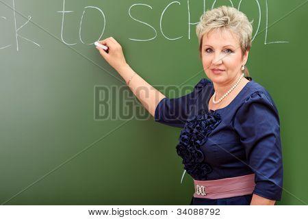 Portrait of a smiling teacher writing on a blackboard.