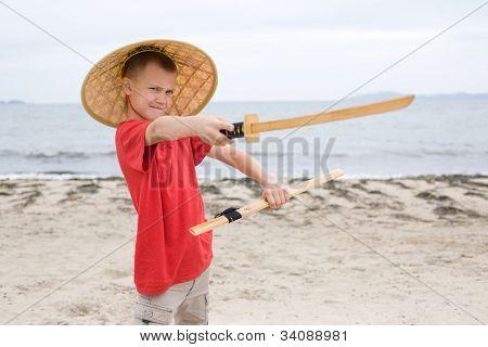 Boy plays with a samurai sword made of bamboo.