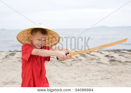 Boy playing with children's katana made of bamboo.