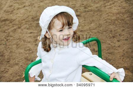 Glückliches niedliche Mädchen tragen weiße Panama Fahrten auf kleinen Karussell auf Spielplatz