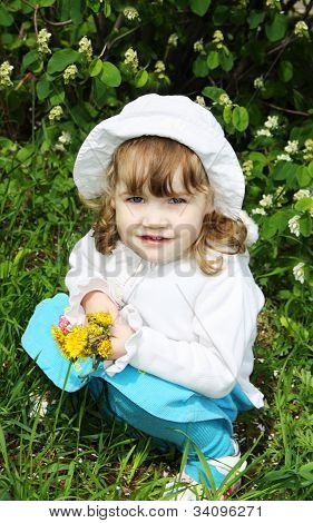 Beautiful Little Girl Wearing White Panama Holds Yellow Dandelions And Sits On Grass