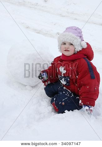 Little Tired Girl Wearing Warm Jumpsuit Sits On Snow Near Big Snowball